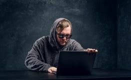 Brodaty hacker w szarym pulowerze i okularach przeciwsłonecznych siedzi przy czarnym stołem obrazy stock