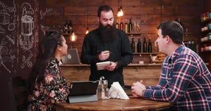 Brodaty kelner bierze rozkaz od pary zbiory wideo
