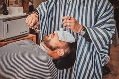 Brodaty klient właśnie dostać dobrego beardcare od modnego fryzjera męskiego zdjęcia royalty free