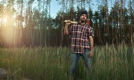 Brodaty Lumberjack trzyma dużą cioskę na ramieniu w pierwszych planach w kapeluszu Obrazy Royalty Free