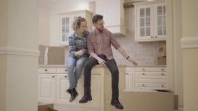 Brodaty mężczyzna i ładny kobiety obsiadanie na stole w kuchni nowy mieszkanie Rodzina dyskutuje plany o nowym mieszkaniu zbiory