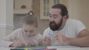 Brodaty mężczyzna patrzeje jego mała dziewczynka rysunek z markierami podczas gdy siedzący przy stołem w domu Ojciec radzi jego zdjęcie wideo