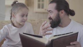 Brodaty mężczyzny obsiadanie na kanapa seansu książce jego mała córka zamknięta w górę Pojęcie szczęśliwa rodzina mała dziewczynk zbiory wideo