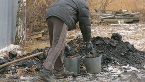 Brodaty mężczyzna ładuje węglową łopatę w zimie w Rosyjskiej wiosce zbiory