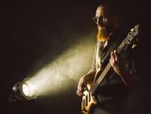 Brodaty mężczyzna bawić się basową gitarę z światłem reflektorów zdjęcie royalty free