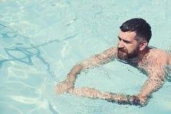 Brodaty mężczyzna dopłynięcie w błękitne wody Wakacje i podróż ocean Relaksuje w zdroju pływackim basenie, orzeźwienie i zdjęcie royalty free