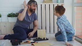 Brodaty mężczyzna jest pomiarowym prześcieradłem drewno z rolką podczas gdy robić constructon pracie z jego synem wtedy robi wyso zdjęcie wideo