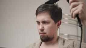 Brodaty mężczyzna jest suszarniczym włosy po tym jak płuczkowy kierowniczy, używać hairdryer, zakończenie zbiory wideo