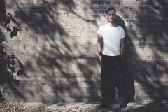 Brodaty mężczyzna jest ubranym pustego białego tshirt i czarnych cajgi z tatuażem Cegły ściany tło horyzontalny Mockup Fotografia Royalty Free