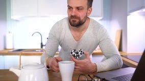 Brodaty mężczyzna ma śniadanie w kuchni i używa laptop zdjęcie wideo