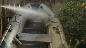 Brodaty mężczyzna myje PVC łódź z wysokim ciśnieniowym zlew na tle drewniany ogrodzenie w jego ogródzie w zdjęcie wideo