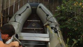 Brodaty mężczyzna myje PVC łódź z wysokim ciśnieniowym zlew na tle drewniany ogrodzenie w jego ogródzie w zbiory