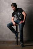Brodaty mężczyzna obsiadanie na prętowej stolec greaser Fotografia Royalty Free