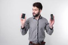 Brodaty mężczyzna odizolowywający na lekkim tle trzyma nowożytnego smartphone starego telefon komórkowego z guzikami i obraz stock