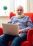 Brodaty mężczyzna odpoczywa na krześle z laptopem Obrazy Royalty Free
