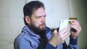 Brodaty mężczyzna płaci dla zakupu w online sklepie używać telefon i kartę kredytową zdjęcie wideo