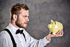 Brodaty mężczyzna patrzeje prosiątko banka w białym łęku krawacie i koszula Zdjęcie Stock