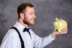 Brodaty mężczyzna patrzeje prosiątko banka w białym łęku krawacie i koszula Obrazy Stock