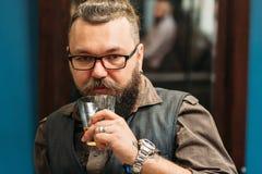 Brodaty mężczyzna pije whisky portret Fotografia Royalty Free