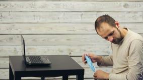 Brodaty mężczyzna pracuje przy komputerem i ka zbiory wideo