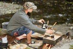 Brodaty mężczyzna przygotowywa kawę w górach Carpathians, Ukraina Fotografia Stock