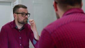Brodaty mężczyzna szczotkuje jego zęby w łazience w ranku Ranek higiena zbiory