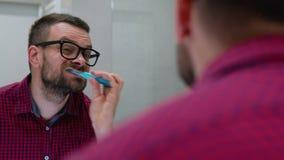 Brodaty mężczyzna szczotkuje jego zęby w łazience w ranku Ranek higiena zbiory wideo
