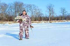 Brodaty mężczyzna trzyma marznącej ryba po pomyślnego zima połowu przy zimnym słonecznym dniem Zdjęcia Royalty Free