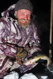 Brodaty mężczyzna trzyma rybi i ono uśmiecha się przy ciemną zimy nocą Obraz Royalty Free