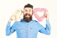 Brodaty mężczyzna trzyma symbole miłość Modniś z sercem, miś i szczęśliwa radosna twarz, Macho z broda uśmiechami obraz royalty free