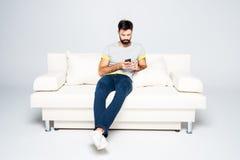 Brodaty mężczyzna używa smartphone Zdjęcia Royalty Free