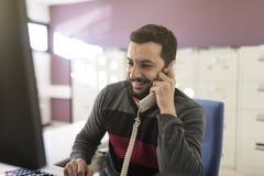 Brodaty mężczyzna w biurze przy telefonem z nastrojowy lekki opowiadać zdjęcia royalty free