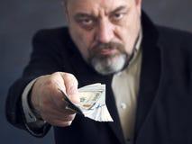 Brodaty mężczyzna w czarnym kostiumu daje pieniądze corruptness Bezprawne operacje zdjęcie royalty free