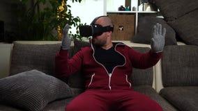 Brodaty mężczyzna w czerwonej całkowitej sztuce VR lub rzeczywistość wirtualna szkła gemowi zbiory wideo