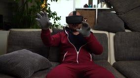 Brodaty mężczyzna w czerwonych całkowitych i specjalnych rękawiczkach bawić się VR lub rzeczywistość wirtualna szkła gemowych zdjęcie wideo