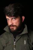 Brodaty mężczyzna w khakiej kurtce z ciekawym spojrzeniem zakończenie W górę czerń Obrazy Stock