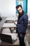 Brodaty mężczyzna w kostiumu z laptopem i filiżanką kawy w kawiarni; Obrazy Royalty Free