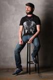 Brodaty mężczyzna w koszulce z motylim obsiadaniem na prętowej stolec greaser Zdjęcia Stock
