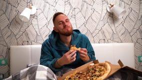 Brodaty mężczyzna w zielonym bathrobe w sypialni na łóżku je pizzę cieszy się je zwolnione tempo zbiory