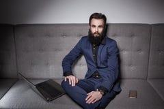 Brodaty mężczyzna wyszukuje internet ubierał w kostiumu i z laptopem; Zdjęcia Royalty Free