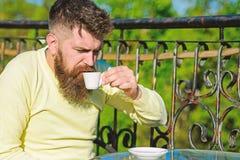 Brodaty mężczyzna z kawy espresso filiżanką, napoje kawowi Mężczyzna z brodą i wąsy na surowej twarzy, ogrodzenie taras na tle zdjęcia royalty free