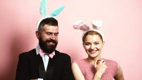 Brodaty mężczyzna z ucho zając i blondyn kobietą z ucho zając je jabłka na różowym tle Kobieta z królików ucho zbiory wideo