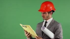 Brodaty męski inżynier patrzeje wprawiać w zakłopotanie podczas gdy czytający dokument zbiory