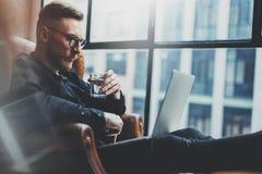 Brodaty młody biznesmen pracuje przy nowożytnym loft biurem Mężczyzna obsiadanie w rocznika krześle, mienie w ręki szkle Obraz Royalty Free