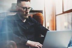 Brodaty młody biznesmen pracuje w nowożytnym loft biurze Obsługuje używać współczesnego notatnika w rocznika krześle podczas gdy  Obraz Royalty Free