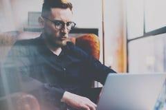 Brodaty młody biznesmen w eyeglasses pracuje w biurze Obsługuje używać współczesnego notatnika w rocznika krześle podczas gdy sie Fotografia Stock