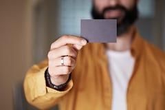 Brodaty młody człowiek daje ręce pustej czarnej wizytówce na zamazanym tle Mockup kopii pasty pustego miejsca reklama obrazy stock