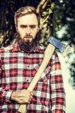 Brodaty młody człowiek trzyma starego ax na drzewnym natury tle w w kratkę koszula, plenerowym obrazy stock