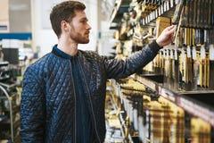 Brodaty młody człowiek w narzędzia sklepie fotografia stock
