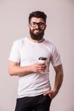 Brodaty młody człowiek z filiżanką i ono uśmiecha się Zdjęcie Stock